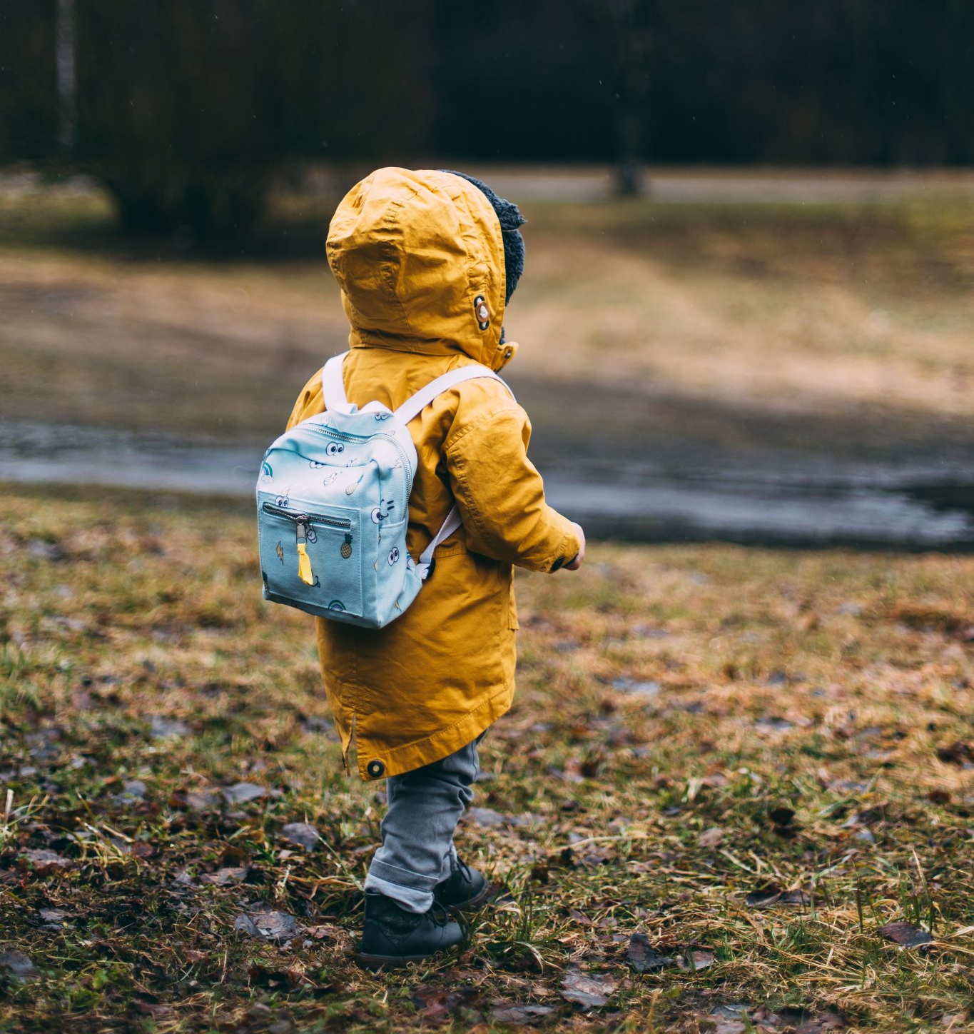 Toddler in yellow coat and backpack in the park