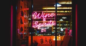 YesMore Agency marketing advice for drinks retailers and off-licences during coronavirus - image of wine and spirits neon sign in bottle shop