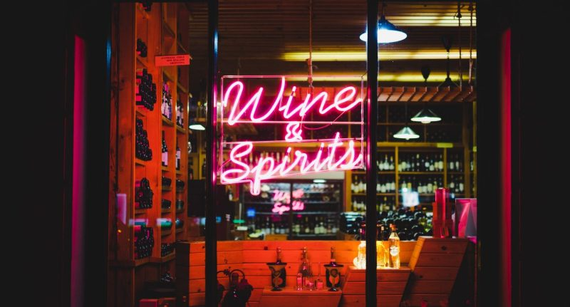 YesMore Wine Marketing Agency marketing advice for drinks retailers and off-licences during coronavirus - image of wine and spirits neon sign in bottle shop