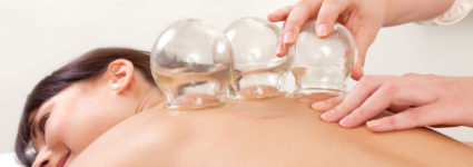 Acupuncture therapist removing a fire cupping glass from the back of a young woman