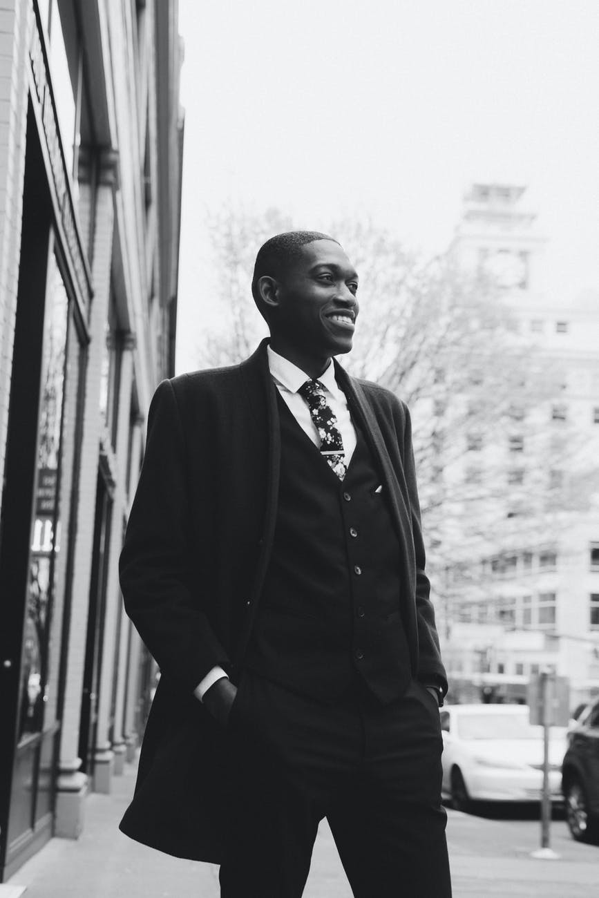 black stylish man in suit standing on street