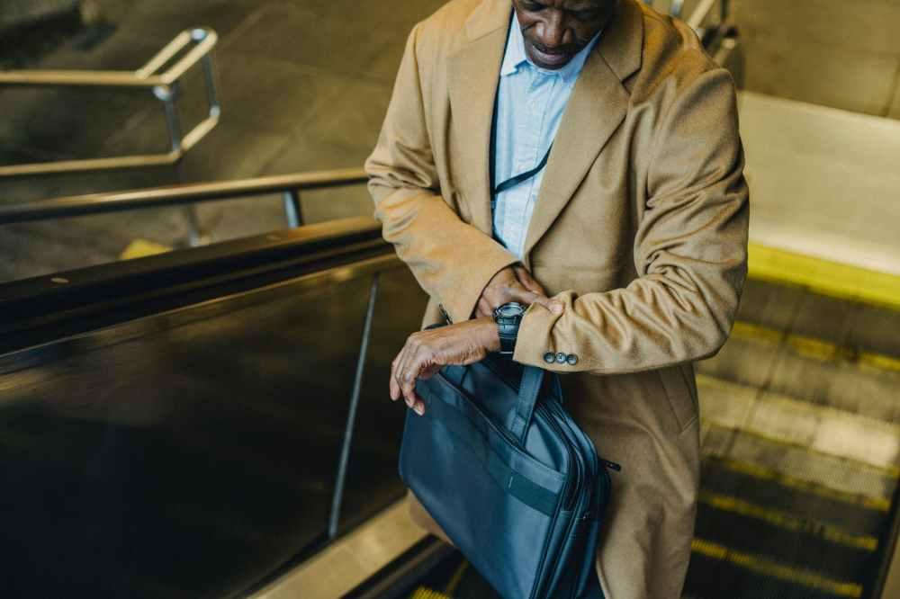 crop black businessman riding escalator and looking at wristwatch