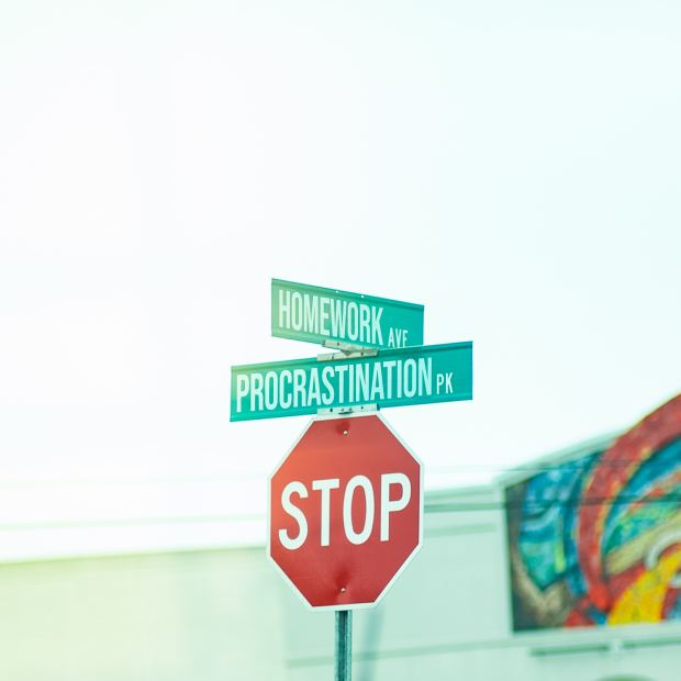 Why do we procrastinate and how to stop it depicted by signage reading stop procrastnation