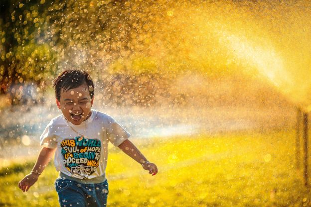 Happiness is a choice depicted by a boy running happily against the background of yellow flowers