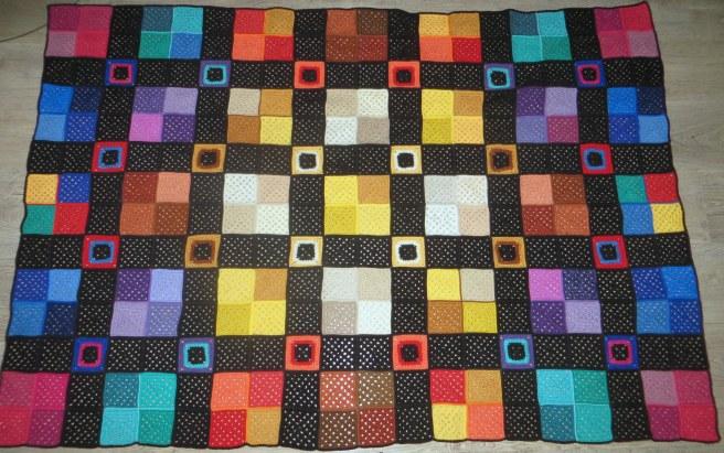 Granny square deken gehaakt van restjes.