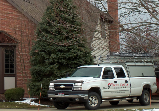 house with Yoders Roofing Truck