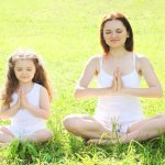 Mother And Child Doing Yoga Meditating On Grass In Pose Lotus