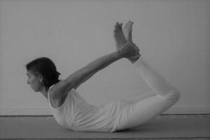 """Dr. Mohme ist die ärztliche & medizinische & fachliche Leitung der Yogalehrer Ausbildung in Berlin. Dr. Mohme verfügt über vielfache medizinische & yogische Qualifikationen. Hier zeigt sie das Asana """"Bogen"""". Manche nennen dieses Asana auch """"halber Bogen"""". Das Sanskritwort für dieses Asana lautet """"Dhanurasana""""."""