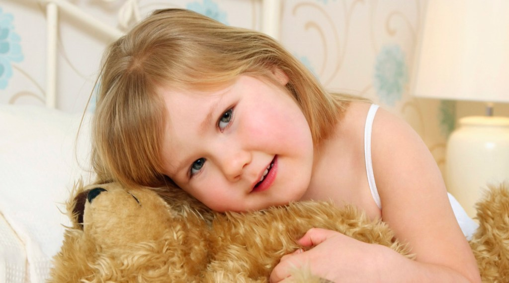 Child on Bed with Teddy Bear