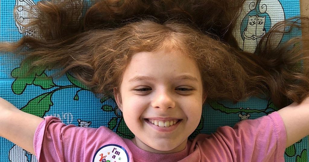 girl smiling on yoga mat