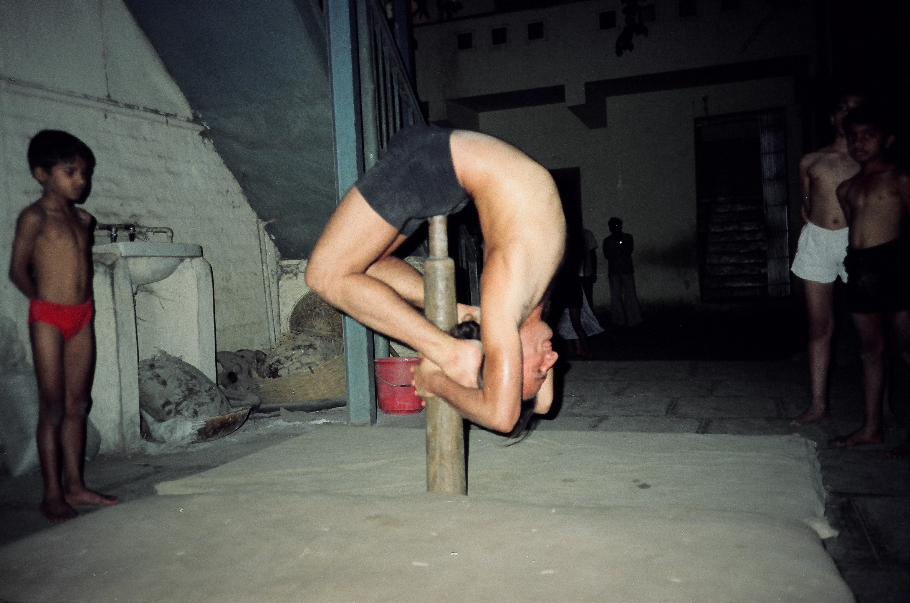 Simon Borg-Olivier practicing kapotasana on a short fixed pole Mallakhamb in Pune, India, 1988