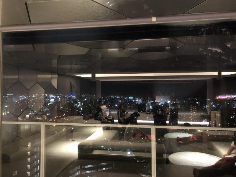 ホテルの最上階でガラスに写ったヨガをする生徒