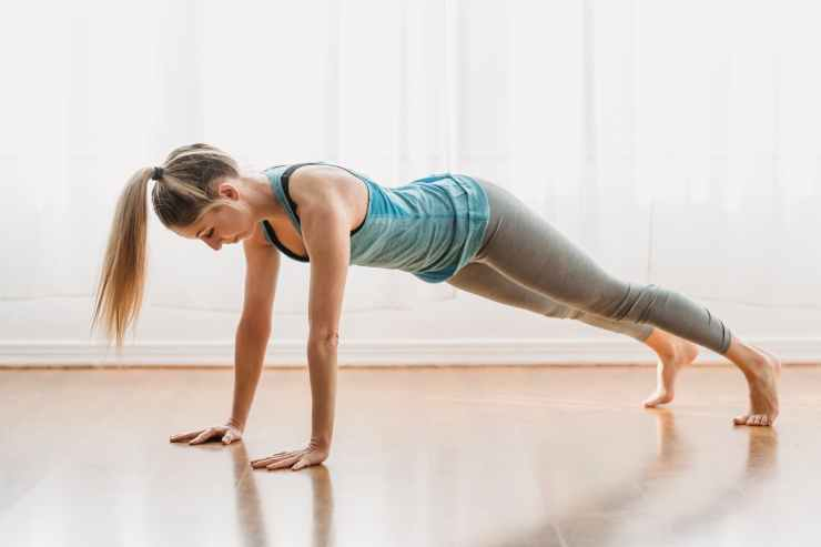 sportive woman doing plank in room