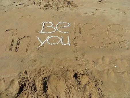 Believe in yourself written in the sand