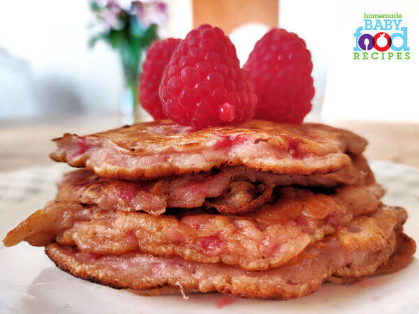 A stack of raspberry pancakes topped with fresh raspberries