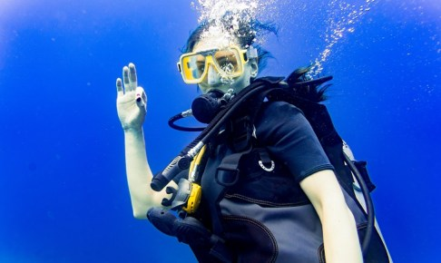 Woman scuba diving in her vacation on coral reef giving the ok sign