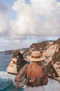 stylish woman standing on cliff against sea