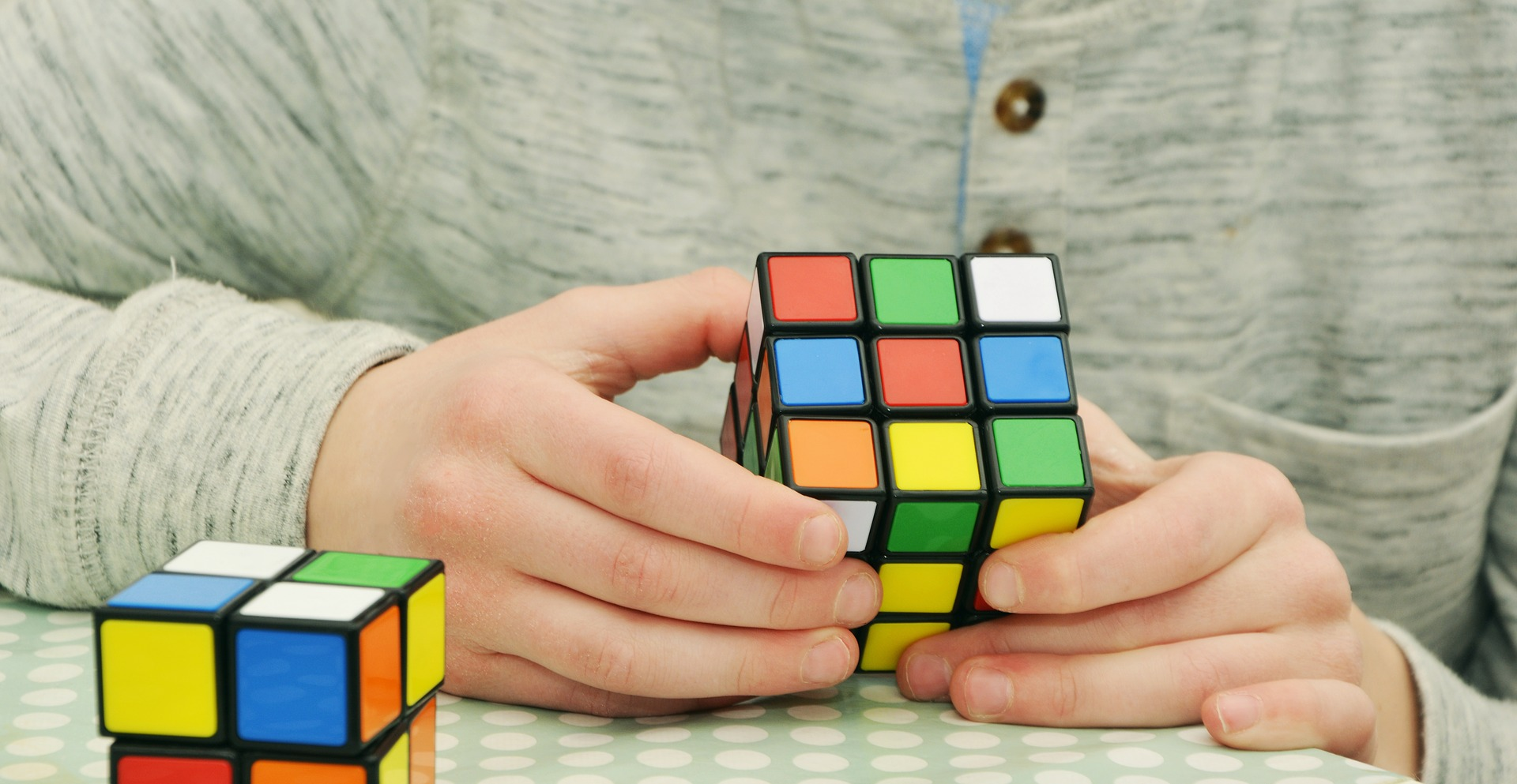 A person wearing a beige and grey patterned button up sweater holds an unsolved 3x3 rubik