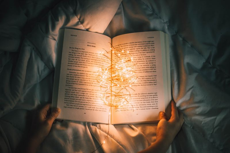 Someone holds the sides of a book, sitting open on a pile of blankets. The room is dark and the pages of the book are illuminated only by a bundle of yellow fairy lights.