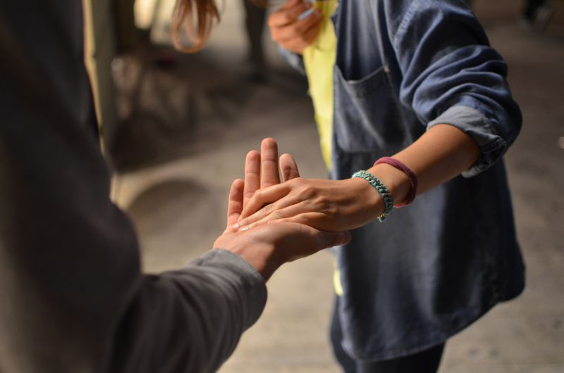 A person wearing a yellow shirt, baggy denim jacket, and colorful braided bracelets, warmly takes the hand of another person, leading them towards something hopeful. Only their torsos and arms are visible.