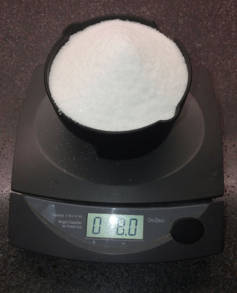 A cup of sugar is on a grey digital scale. The display shows 0 pounds, 8.0 ounces.