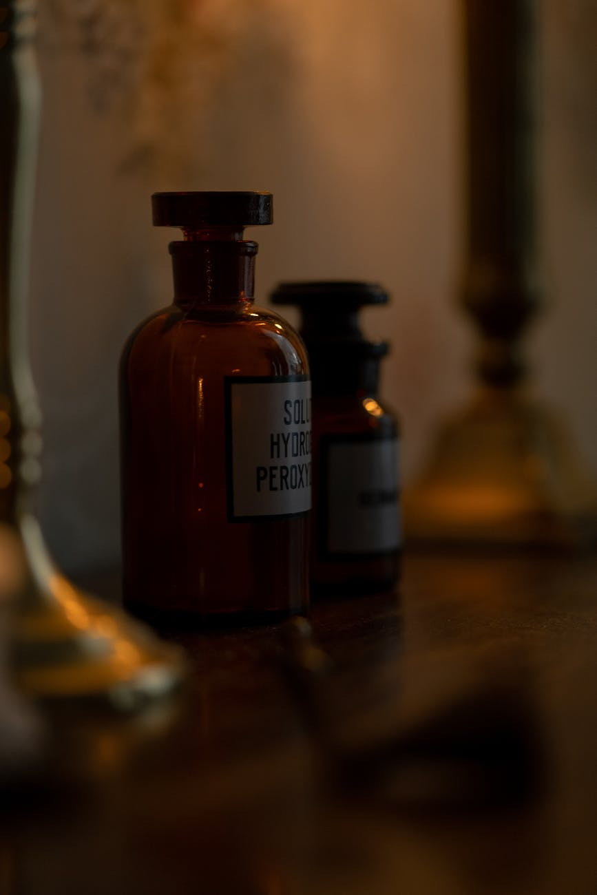 brown glass bottle on brown wooden table