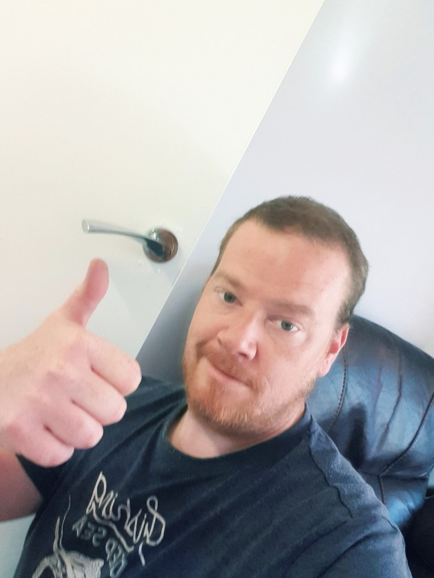 A thumbs up selfie of me after finishing fitting the new door handles.