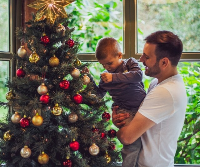 A father and his son hanging decorations on their christmas tree, preparing for the festivities of a Covid Christmas.