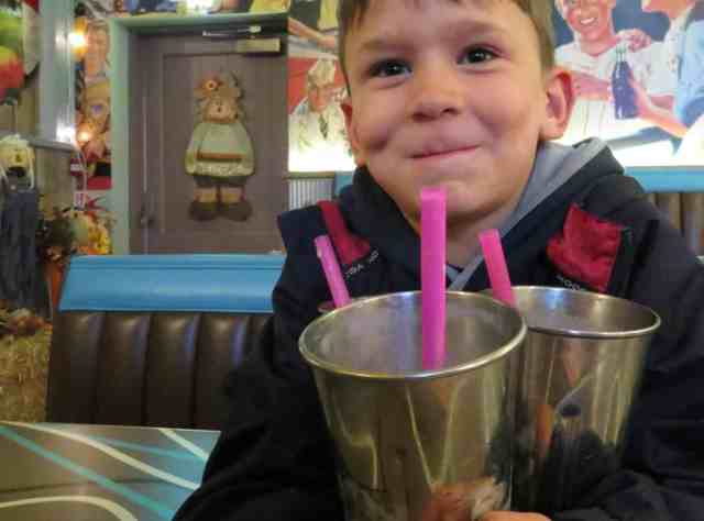 Boy with milkshakes at Billy Bobs Ice Cream Parlour on a rainy day