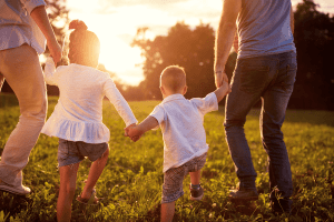 young family of four running together while holding hands
