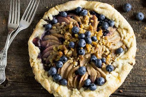 rustic pear and blueberry galette on board table with two antique silver forks to the left