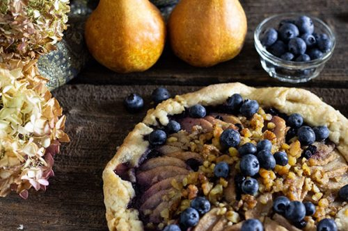 overhead shot of  whole  pear and blueberry galette with two bosc pears, tiny glass bowl of blueberries and dried hydrangea heads to the left on a barn board table