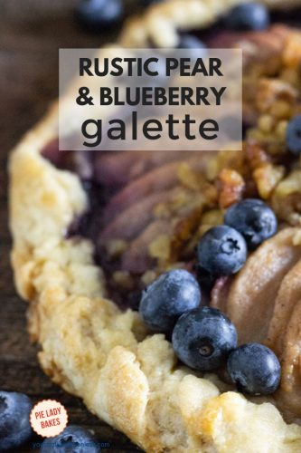 close up side view of pear and blueberry galette with 5 blueberries in sharp focus and the text rustic pear and blueberry galette in black on a white overlay box