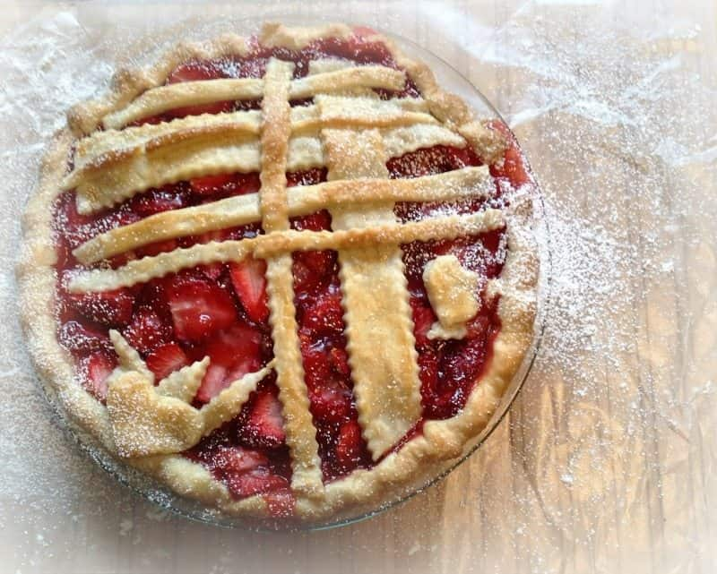 overhead shot of strawberry pie with pie crust lattice and sprinkled with powdered sugar, sitting on parchment paper