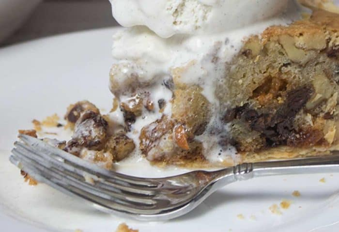 chocolate chip cookie pie with bite removed, fork to the side and ice cream over all