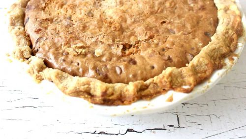 overhead image of freshly baked toll house cookie pie in white pie plate