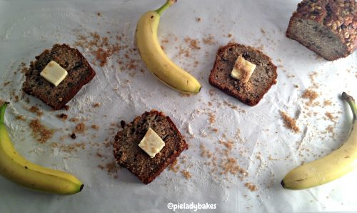 3 slices of homemade banana bread with pats of butter and three whole bananas on waxed paper