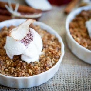 two white ramekins of baked apple crisp, whipped cream and apple chip on top