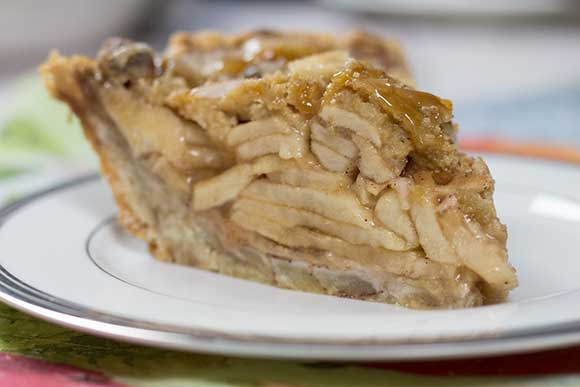 Slice of Apple Pie with cinnamon roll pie crust on a white pie plate