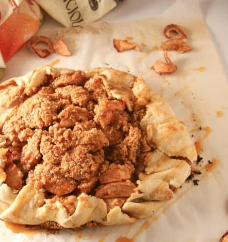 overhead shot of baked apple galette on parchment paper with apple print napkin in the background