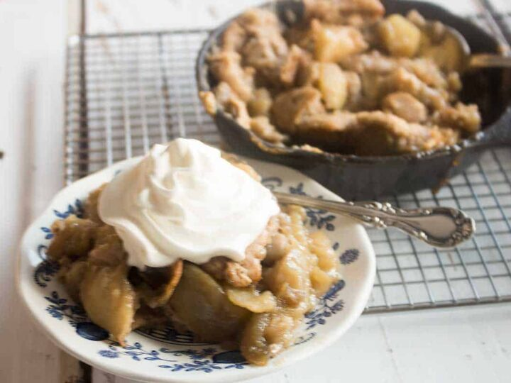 serving of baked apple cobbler with whipped cream on a blue and white plate with antique silver spoon and skillet of apple pandowdy in the background