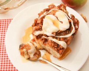 big slice of apple pie coffee cake on a white plate, with spoon, walnuts and apple to the side