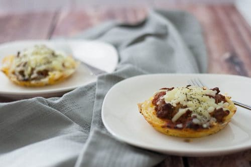 two servings of spaghetti pie casserole on white plates with gray napkin