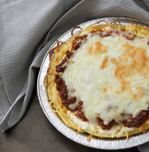 overhead view of whole spaghetti pie in aluminum foil tin and topped with mozzarella cheese