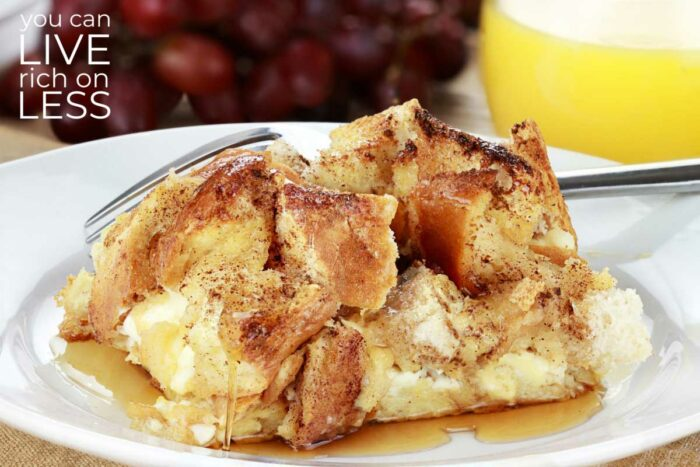 french toast bake on a white plate with grapes and orange juice in the background