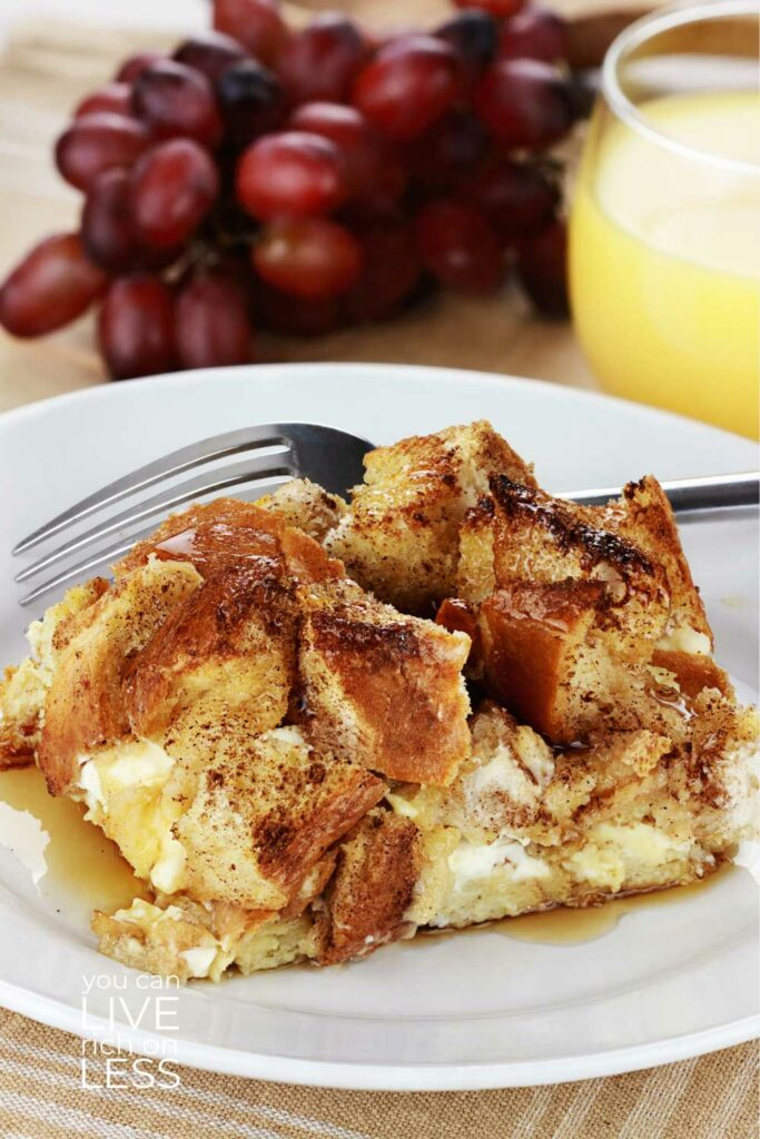overnight french toast casserole on a white plate with maple syrup red grapes and a glass of orange juice in the background