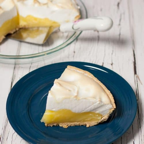 slice of lemon meringue pie on a blue plate with pie and pie server in the background.