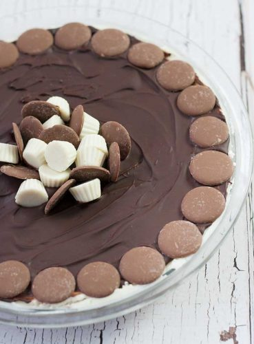 overhead image of nanaimo bar pie decorated with dark and white chocolates, and milk chocolate buttons around the edge of the pie plate