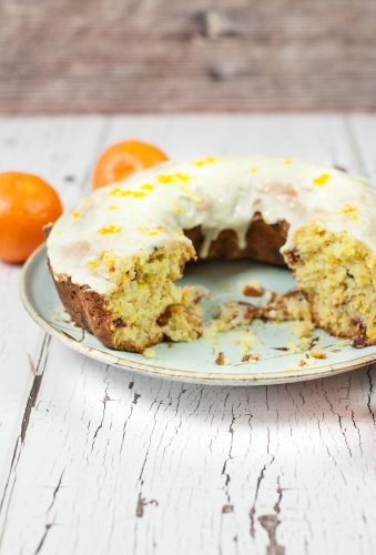 orange cranberry pound cake on a blue plate with slices removed cake has thick orange cranberry glaze with two oranges in the background on a weathered white wooden table
