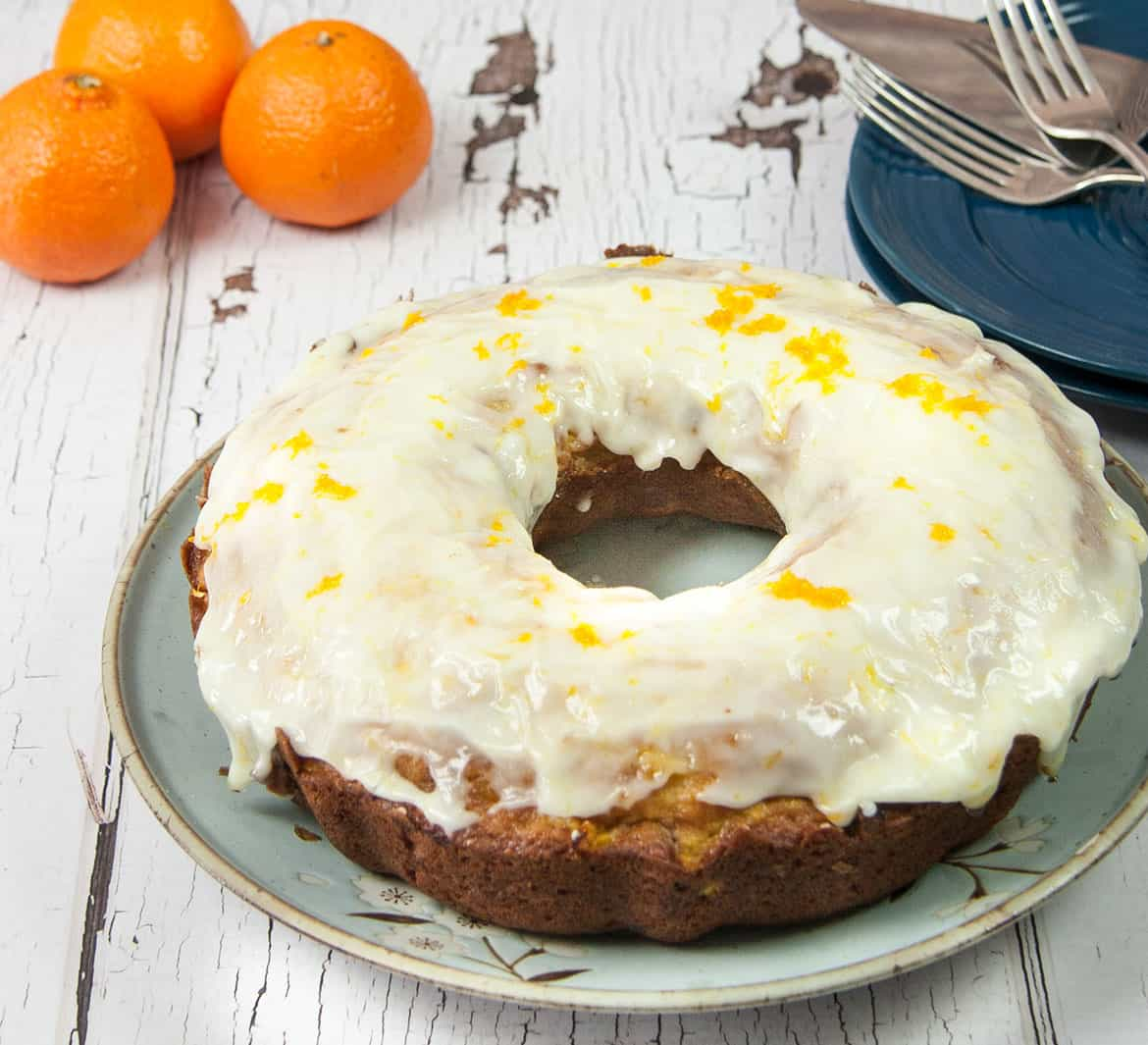 orange cranberry bundt cake with thick orange cranberry glaze orange zest on top blue plates and silver forks in right background three oranges in left background on white weathered wood table